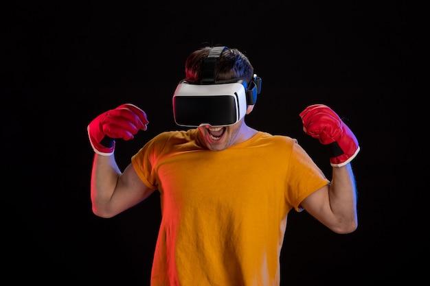 Jonge man virtual reality spelen in mma handschoenen op donkere ondergrond