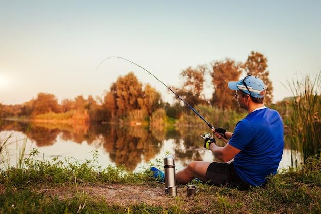 Jonge man vissen op de rivier bij zonsondergang