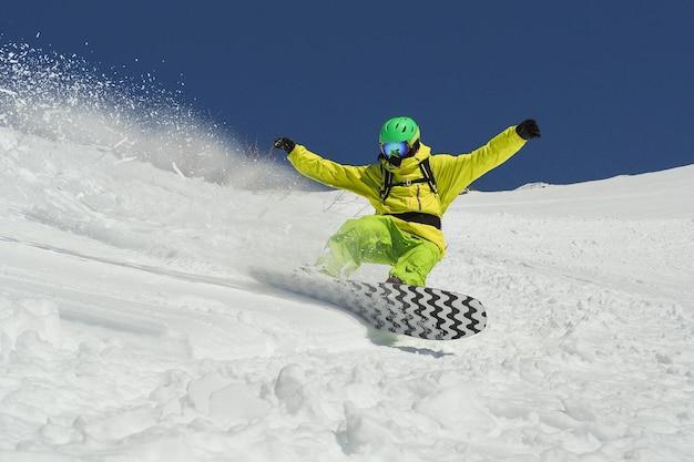 Jonge man vliegen op snowboard op poedersneeuw