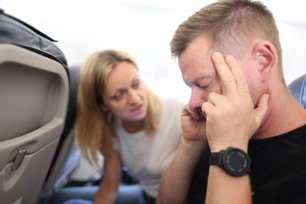 Jonge man vliegt in het vliegtuig en houdt een pijnlijk hoofd vast