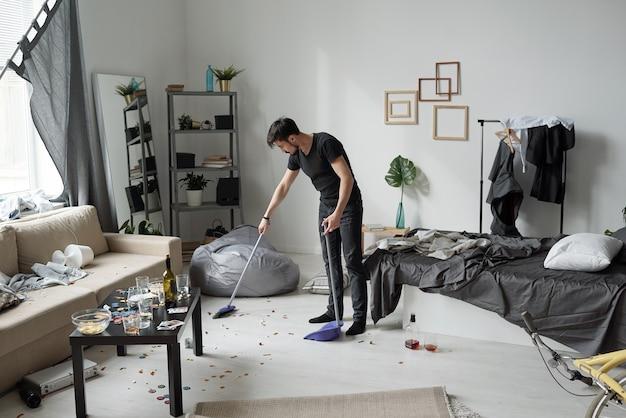 Jonge man vloer thuis na feest vegen: flessen, kruimels en pokerfiches op de vloer