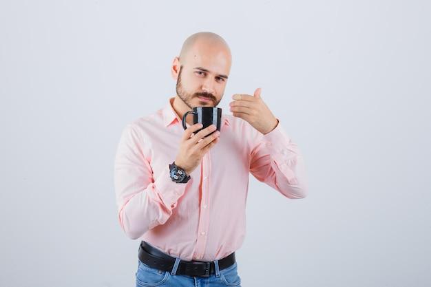Jonge man voelt een frisse geur in roze shirt, spijkerbroek, vooraanzicht.