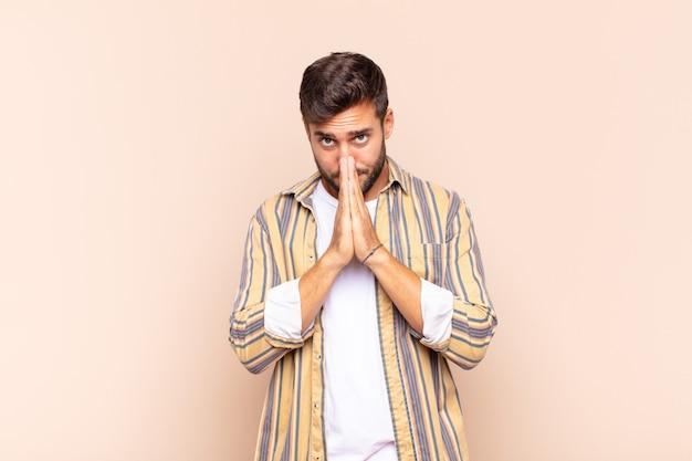 Jonge man voelt zich bezorgd, hoopvol en religieus, bidt trouw met de handpalmen ingedrukt, smeekt om vergeving