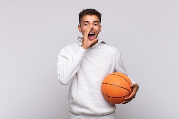 Jonge man voelt zich blij, opgewonden en positief, geeft een grote schreeuw met de handen naast de mond, roept. mand concept