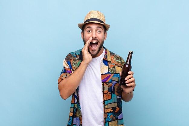 Jonge man voelt zich blij, opgewonden en positief, geeft een grote schreeuw met de handen naast de mond, roept. vakantie concept