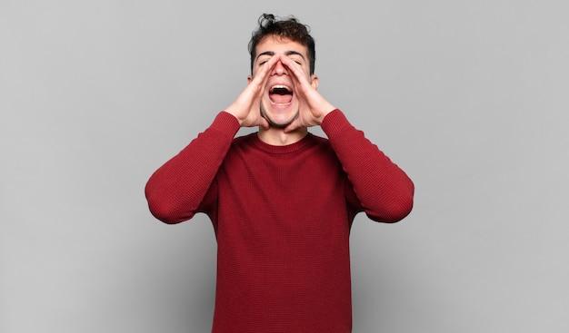 Jonge man voelt zich blij, opgewonden en positief, geeft een grote schreeuw met de handen naast de mond, roept