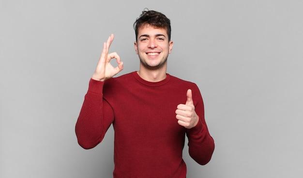Jonge man voelt zich blij, verbaasd, tevreden en verrast, toont oké en duimen omhoog gebaren, glimlachend