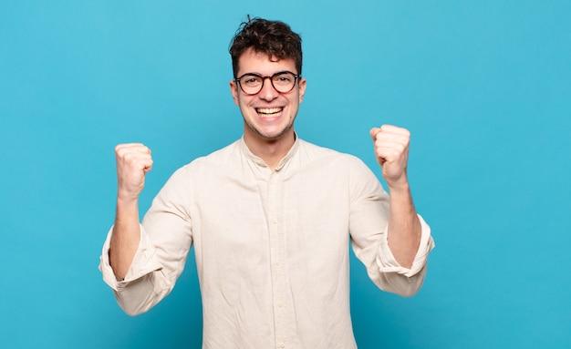 Jonge man voelt zich blij, verrast en trots, schreeuwt en viert succes met een grote glimlach