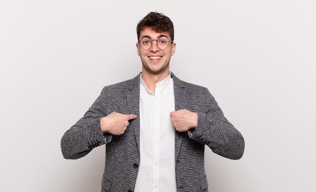 Jonge man voelt zich blij, verrast en trots, wijst naar zichzelf met een opgewonden, verbaasde blik