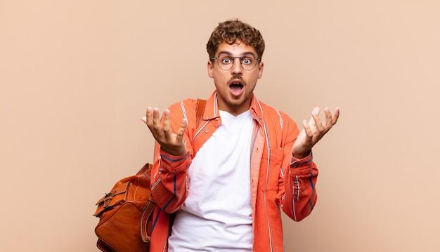 Jonge man voelt zich extreem geschokt en verrast, angstig en in paniek, met een gestreste en met afschuw vervulde blik. student concept