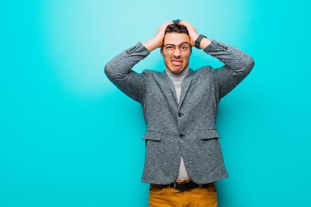 Jonge man voelt zich gefrustreerd en geïrriteerd, ziek en moe van mislukking, beu met saaie, saaie taken tegen blauwe muur
