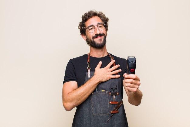 Jonge man voelt zich gelukkig en verliefd, glimlachend met de ene hand naast het hart en de andere naar voren gestrekt Premium Foto
