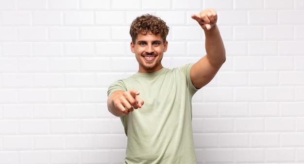 Jonge man voelt zich gelukkig en zelfverzekerd, wijst met beide handen naar voren en lacht, kiest jou
