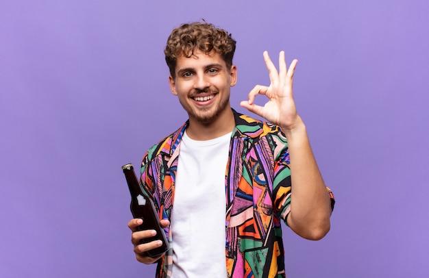 Jonge man voelt zich gelukkig, ontspannen en tevreden, toont goedkeuring met een goed gebaar, glimlachend. vakantie concept
