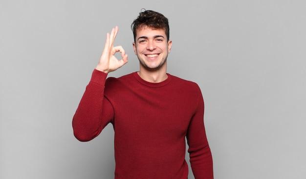 Jonge man voelt zich gelukkig, ontspannen en tevreden, toont goedkeuring met een goed gebaar, glimlachend