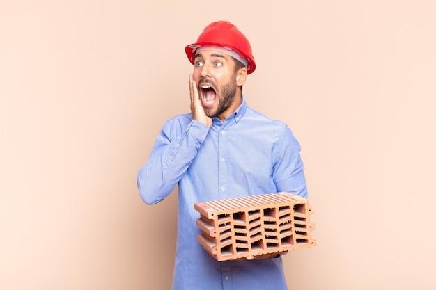 Jonge man voelt zich gelukkig, opgewonden en verrast, kijkend naar de zijkant met beide handen op het gezicht. architect concept