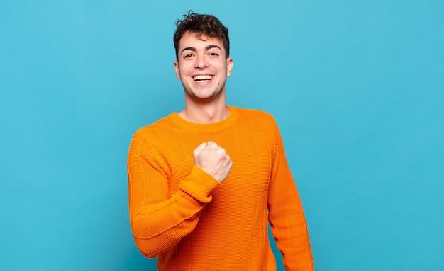 Jonge man voelt zich gelukkig, positief en succesvol, gemotiveerd wanneer hij voor een uitdaging staat of goede resultaten viert