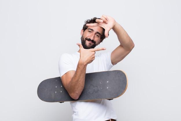 Jonge man voelt zich gelukkig, vriendelijk en positief, lacht en maakt een portret of fotolijst met handen
