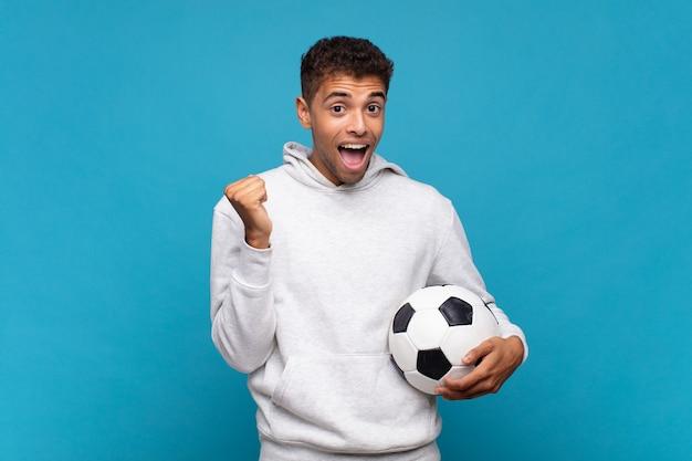 Jonge man voelt zich geschokt, opgewonden en blij, lacht en viert succes, zegt wauw!