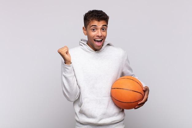 Jonge man voelt zich geschokt, opgewonden en blij, lacht en viert succes, zegt wow !. mand concept