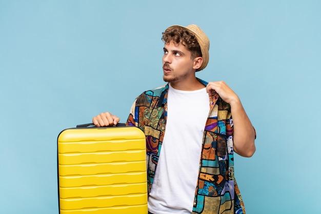 Jonge man voelt zich gestrest, angstig, moe en gefrustreerd, trekt de hals van het shirt aan, kijkt gefrustreerd door het probleem. vakantie concept