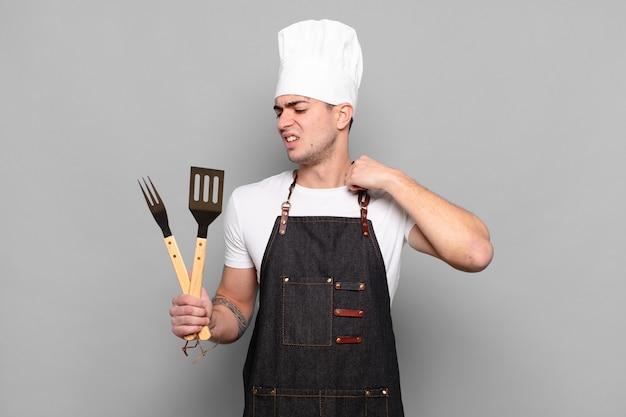 Jonge man voelt zich gestrest, angstig, moe en gefrustreerd, trekt de hals van het shirt aan, kijkt gefrustreerd door het probleem