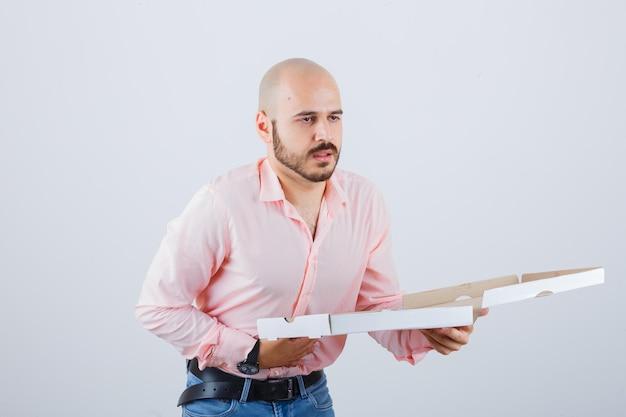 Jonge man voelt zich misselijk in shirt, spijkerbroek en ziet er onwel uit. vooraanzicht.