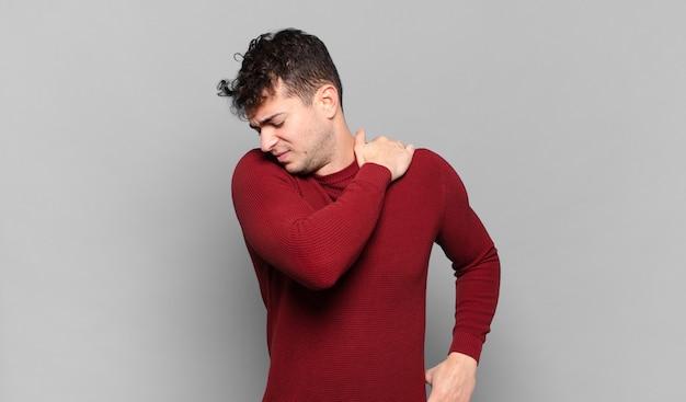 Jonge man voelt zich moe, gestrest, angstig, gefrustreerd en depressief, lijdt aan rug- of nekpijn Premium Foto