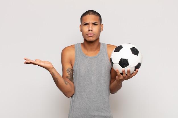 Jonge man voelt zich verbaasd en verward, twijfelt, weegt of kiest verschillende opties met grappige uitdrukking