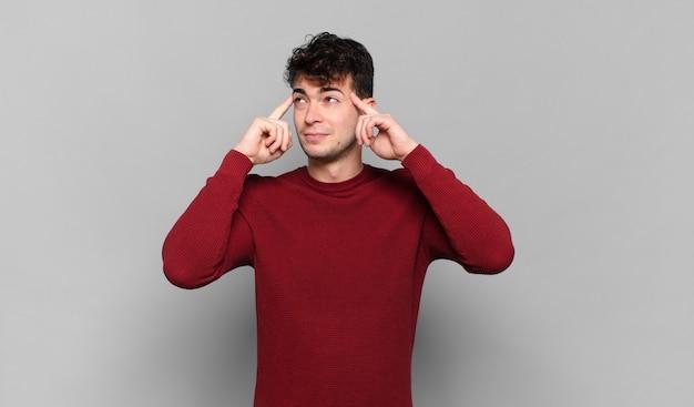 Jonge man voelt zich verward of twijfelt, concentreert zich op een idee, denkt hard, zoekt ruimte aan de zijkant te kopiëren