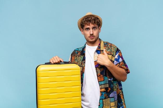 Jonge man voelt zich verward, verbaasd en onzeker, wijst naar zichzelf, vraagt zich af en vraagt wie, ik ?. vakantie concept
