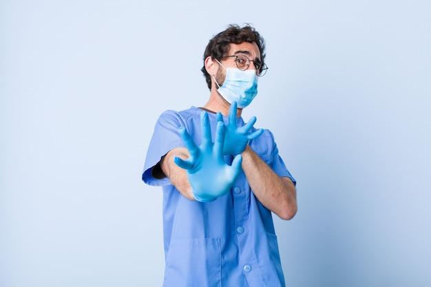 Jonge man voelt zich walgelijk en misselijk en trekt zich terug van iets smerigs, stinkends of stinkends, en zegt bah. coronavirus concept