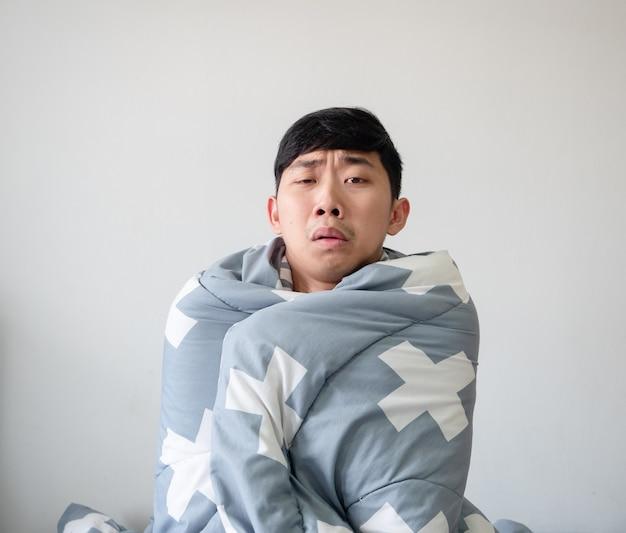Jonge man voelt zich ziek verdrietig bij het gezicht bedekken zijn lichaam door deken op witte achtergrond zieke man concept
