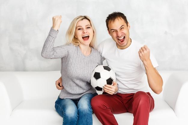 Jonge man voetbal kijken met zijn vrouw thuis