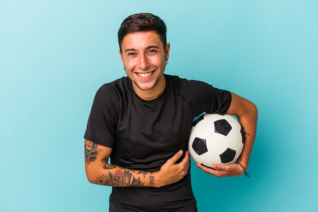 Jonge man voetballen met een bal geïsoleerd op blauwe achtergrond lachen en plezier hebben.
