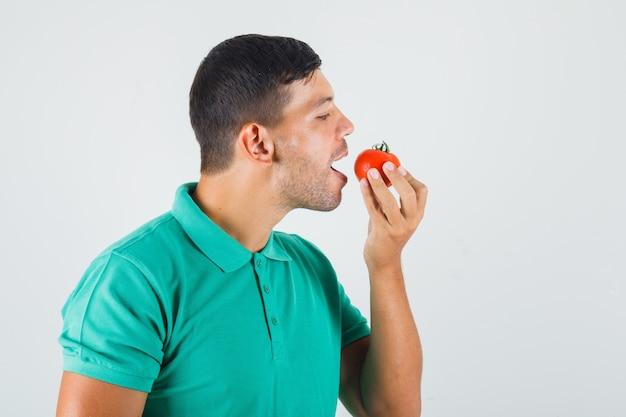Jonge man voorbereiding om tomaat in groenachtig t-shirt te eten.