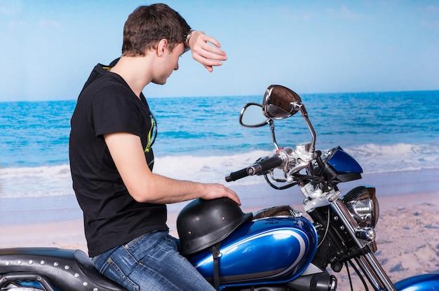 Jonge man voorhoofd afvegen met pols zittend op klassieke blauwe motorfiets op strand en in de verte kijken