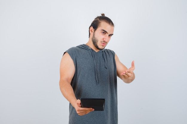 Jonge man vragen vraag gebaar maken in hoodie en op zoek weemoedig, vooraanzicht.