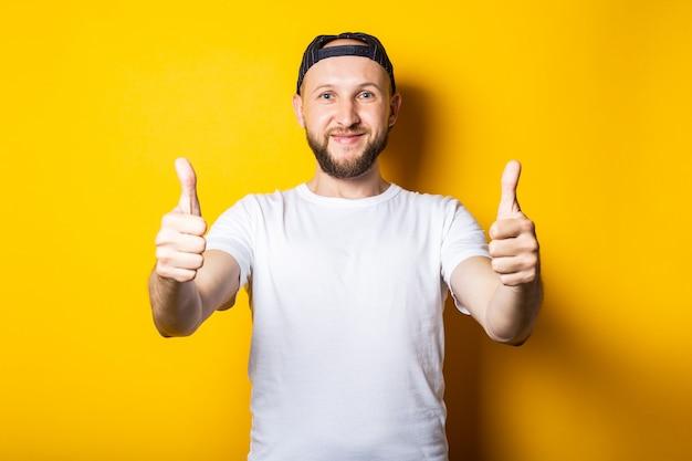 Jonge man vriendelijk en gelukkig in een wit t-shirt en een baseballcap, toont een klasse gebaar, duim omhoog