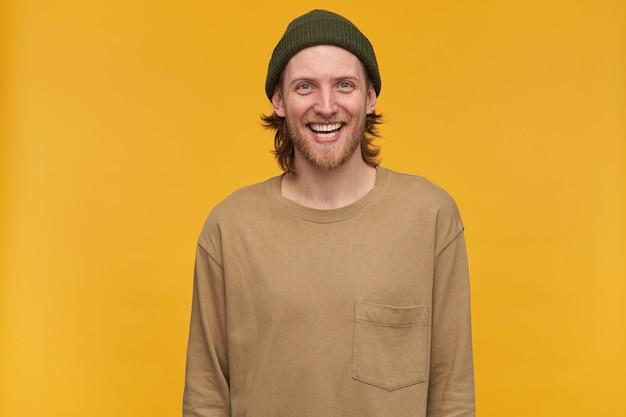 Jonge man, vrolijke man met blond haar, baard en snor. het dragen van een groene muts en een beige trui. en in grote lijnen lachend, geïsoleerd over gele muur