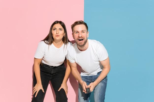 Jonge man, vrouw in casual op roze, blauwe tweekleurige achtergrond.