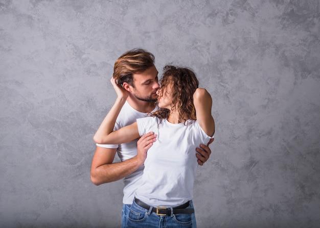 Jonge man vrouw van achteren knuffelen