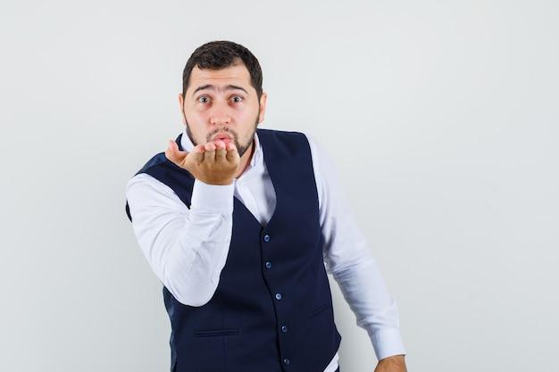 Jonge man waait lucht kus met pruilende lippen in pak en vest