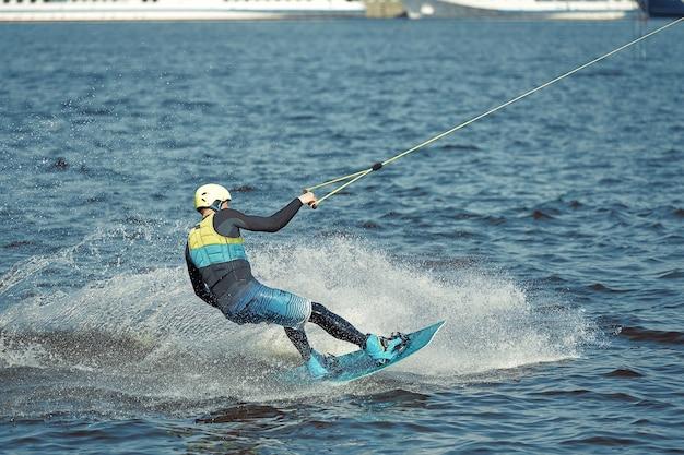 Jonge man wakeboard rijden op een zomer-meer