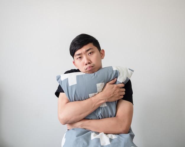 Jonge man wakker en knuffelen kussen kijken camera verveeld gezicht op witte geïsoleerde achtergrond
