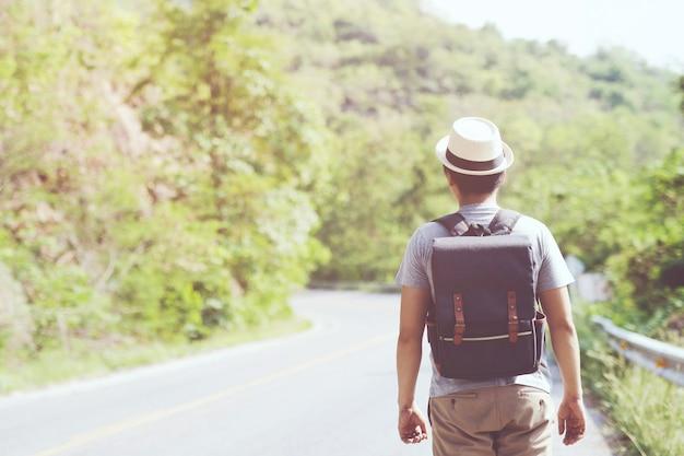 Jonge man wandelen reizen wandelen langs de weg in zomer reizen lifestyle reislust avontuur met rugzak genieten op piek berg
