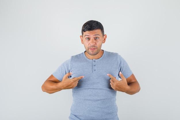 Jonge man wees met zijn vingers naar zichzelf en vroeg 'mij?' in grijs t-shirt en twijfelde