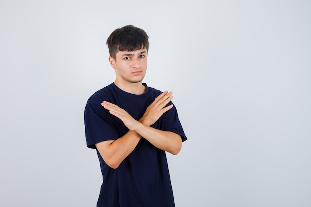 Jonge man weigering gebaar in zwart t-shirt tonen en serieus kijken. vooraanzicht.