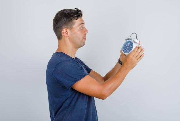 Jonge man wekker instellen in donkerblauw t-shirt en opgewonden kijken.
