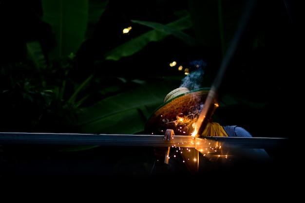 Jonge man werknemer lassen ijzeren stukken op het werk met beschermende bril